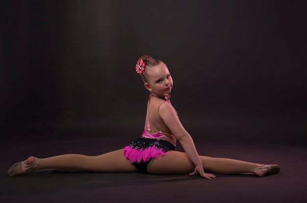 Klein meisje in gymnast zwart en roze kostuum zittend in touw of splitst.