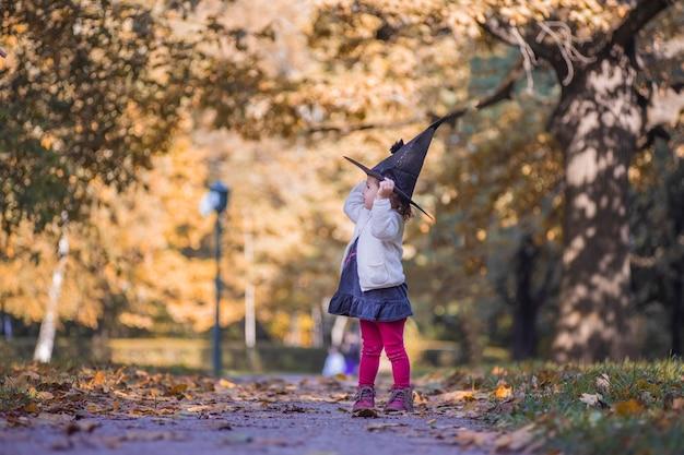 Klein meisje in halloween bos kind spelen in herfst park kinderen plukken rijpe groenten op een boerderij in
