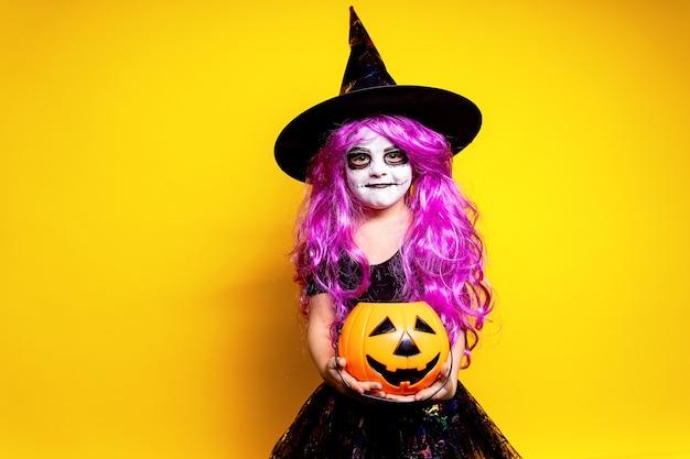 Klein meisje in halloween-heksenkleding en hoed die en gezichten schrikken maken die op gele achtergrond worden geïsoleerd. snoep of je leven.