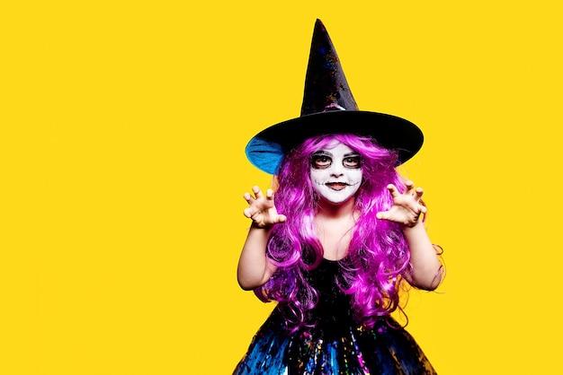 Klein meisje in halloween-heksenkleding en hoed die en gezichten schrikken maken die op gele achtergrond worden geïsoleerd.