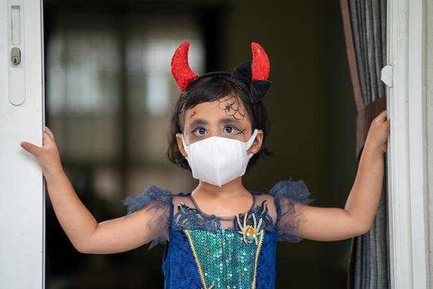 Klein meisje in halloween-kostuum met een beschermend gezichtsmasker dat thuis binnen staat
