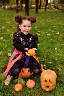 Klein meisje in halloween-kostuum met pompoen die halloween viert