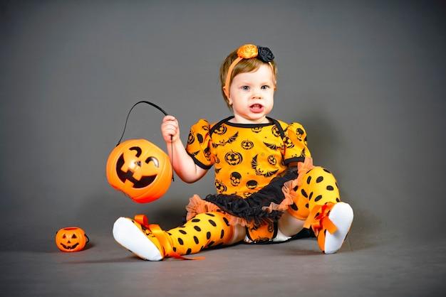 Klein meisje in halloween-kostuum met pompoenhefboom. een kind in de studio, grimassen en afschuw op de vakantie.