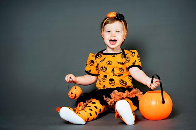 Klein meisje in halloween-kostuum met pompoenhefboom. gelukkig een kind in de studio, grimassen en afschuw op de vakantie.