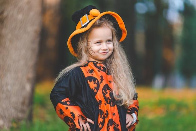 Klein meisje in heksenkostuum staat in het park in de herfst op halloween-vakantie.
