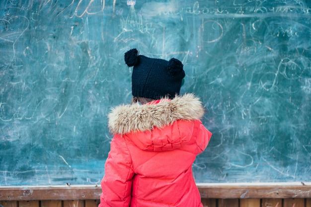 Klein meisje in herfst park staat op het schoolbestuur
