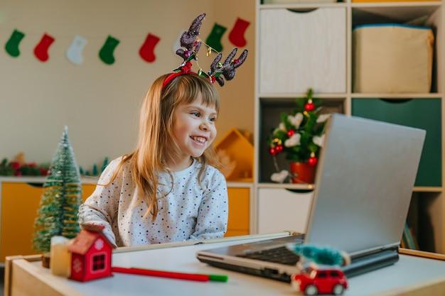 Klein meisje in hertenkostuum met laptop voor videogesprek in de kinderkamer in de kersttijd