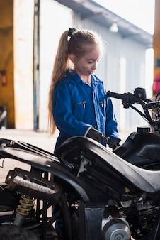 Klein meisje in het algemeen inspecteren quad bike