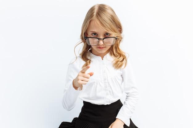Klein meisje in het beeld van een strikte leraar, bril, serieuze blik, grappig en schattig