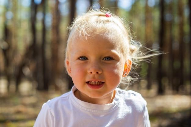 Klein meisje in het bos. loop met de ouders. wandelen met ouders.