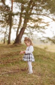 Klein meisje in het bos. op een bosweg tussen de dennen.