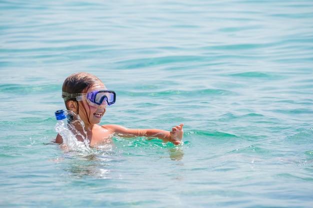 Klein meisje in het masker in de zee, duikt, zwemt. masker en buis om te duiken. glimlachend grappig kind met blauw duikmasker. baden in oceaan. zwemactiviteiten