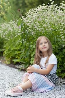 Klein meisje in het park op een zomerdag in de buurt van een bloembed.