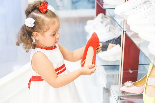 Klein meisje in het winkelcentrum kiest schoenen