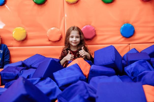 Klein meisje in het zwembad met grote gekleurde blokjes