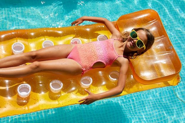 Klein meisje in het zwembad op een opblaasbare matras