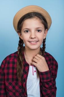 Klein meisje in hoed met pigtails