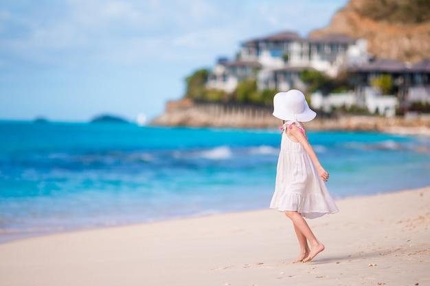 Klein meisje in hoed op het strand tijdens caribische vakantie