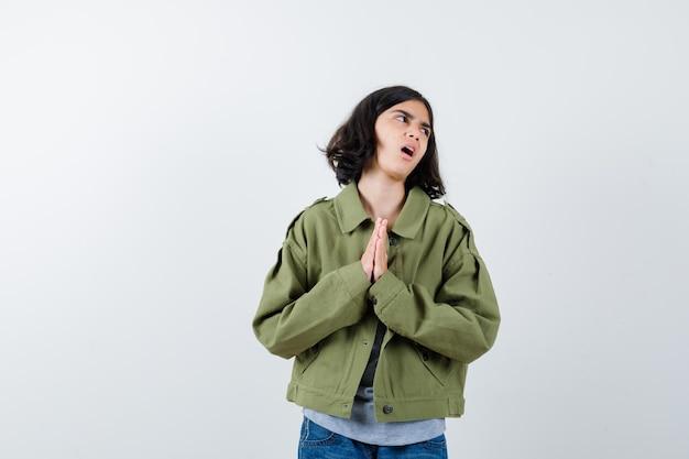Klein meisje in jas, t-shirt, jeans die de handen samendrukt om te bidden en er hoopvol uitziet, vooraanzicht.