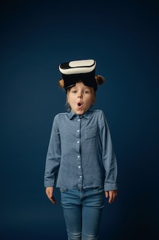Klein meisje in jeans en shirt met virtual reality headset-bril