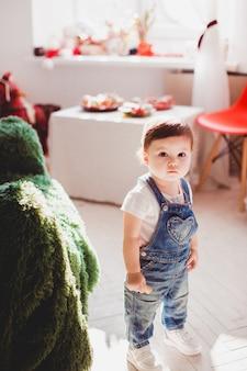 Klein meisje in jeans springers staat in de kamer