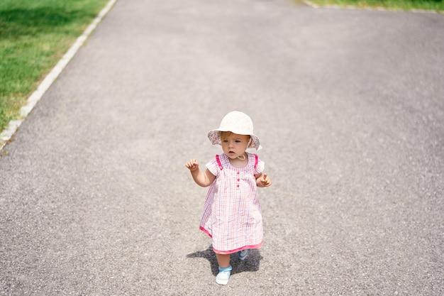Klein meisje in jurk en hoed loopt op het asfalt