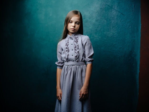 Klein meisje in jurk poseren studio groene achtergrond
