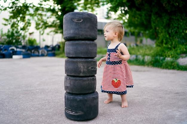 Klein meisje in jurk staat in de buurt van kleine banden