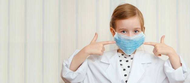 Klein meisje in kamerjas en masker van een dokter laat met een gebaar zien dat iedereen een beschermend masker moet dragen. ruimte voor inscripties