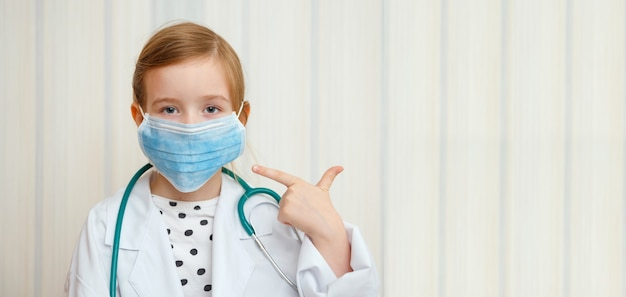 Klein meisje in kamerjas en masker van een dokter laat met een gebaar zien dat iedereen een beschermend masker moet dragen.