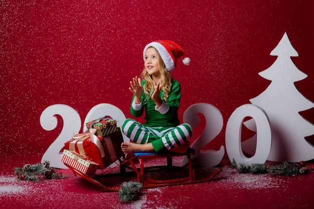 Klein meisje in kerst pyjama of elf kostuum en kerstmuts vangt sneeuw zittend op een slee