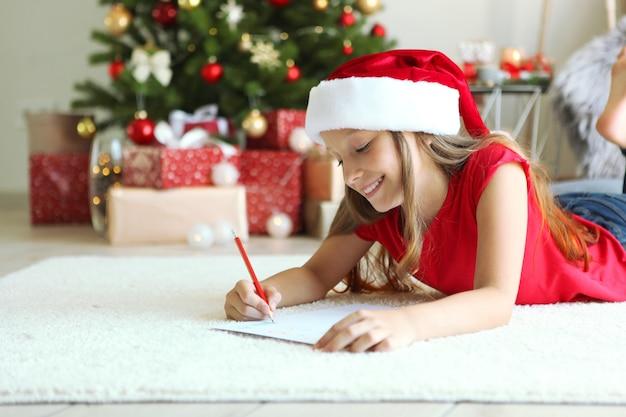 Klein meisje in kerstinterieur schrijft een brief aan de kerstman