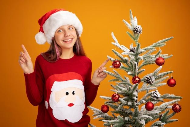 Klein meisje in kerstmissweater en kerstmuts blij en verrast lachend vrolijk naast een kerstboom op oranje achtergrond
