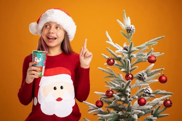 Klein meisje in kerstmissweater en santahoed die kleurrijke document kop houden