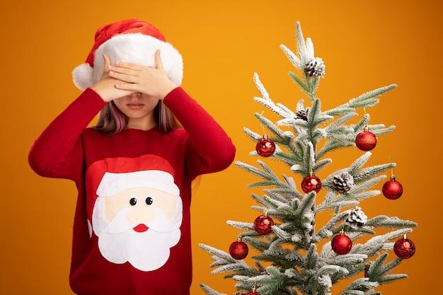 Klein meisje in kerstmissweater en santahoed die ogen met handen sluiten naast een kerstboom op oranje achtergrond