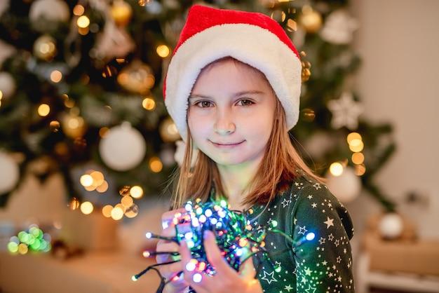 Klein meisje in kerstmuts met sprankelende guirlande in de buurt van kerstboom thuis