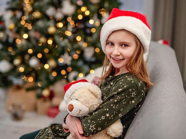 Klein meisje in kerstmuts zittend op de bank in de buurt van de kerstboom thuis