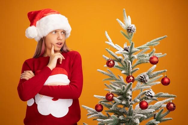Klein meisje in kerstsweater en kerstmuts opzij kijkend verward en verrast naast een kerstboom over oranje achtergrond