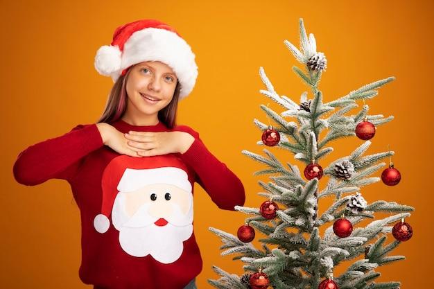 Klein meisje in kersttrui en kerstmuts blij en verrast glimlachend vrolijk hand in hand op haar borst zich dankbaar voelend naast een kerstboom over oranje achtergrond