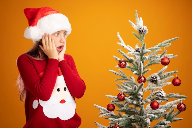 Klein meisje in kersttrui en kerstmuts die naast een kerstboom staat en ernaar kijkt verbaasd en verrast over oranje achtergrond
