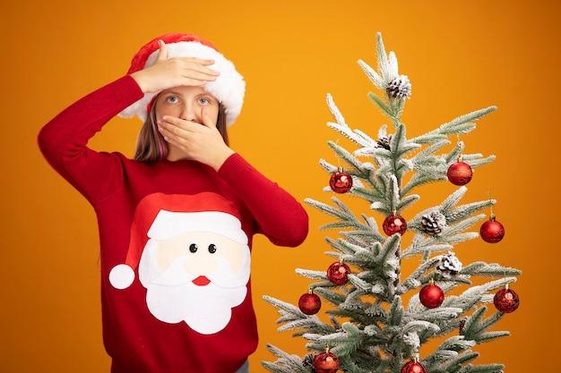 Klein meisje in kersttrui en kerstmuts kijkend naar camera met hand op haar voorhoofd die mond bedekt met andere hand die naast een kerstboom staat over oranje achtergrond