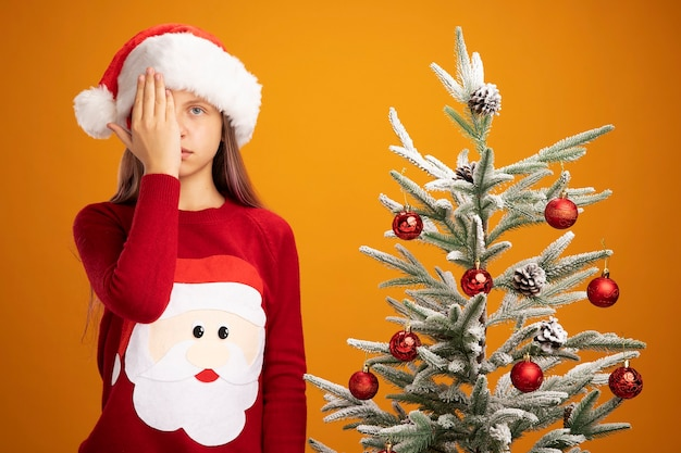 Klein meisje in kersttrui en kerstmuts kijkend naar camera met serieus gezicht dat oog bedekt met hand naast een kerstboom over oranje achtergrond