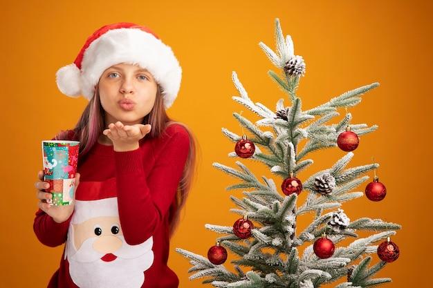 Klein meisje in kersttrui en kerstmuts met kleurrijke papieren beker die een kus blaast naast een kerstboom over oranje achtergrond