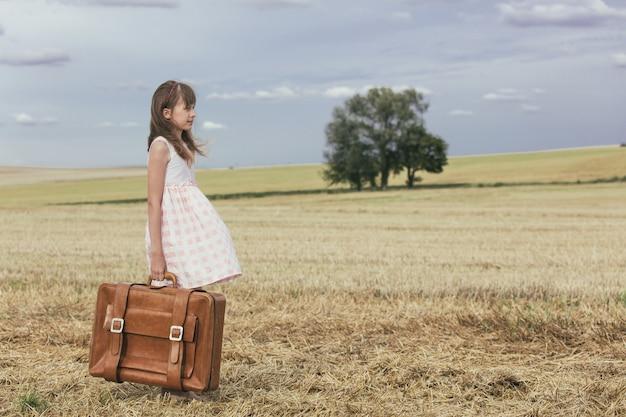 Klein meisje in klassieke jurk met koffer reizen Premium Foto