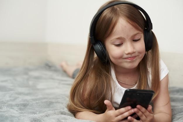 Klein meisje in koptelefoon luisteren naar muziek