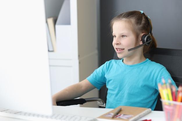 Klein meisje in koptelefoon met microfoon zit achter computerscherm
