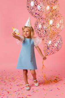 Klein meisje in kostuum met ballonnen en feestmuts