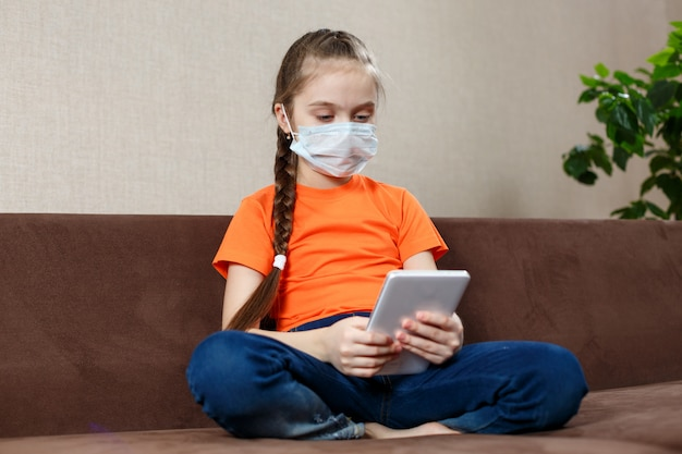 Klein meisje in medische masker zittend op de bank in de lotuspositie en met behulp van tablet pc. isolatie thuis.