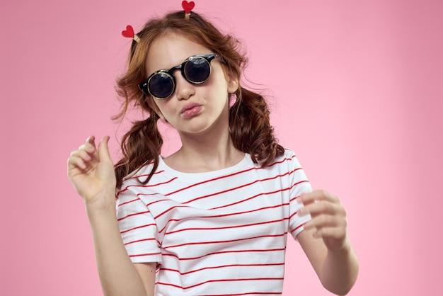 Klein meisje in modieuze glazen en wasknijpers op haar haar emoties roze harten.