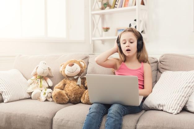 Klein meisje in oortelefoons met laptop thuis. schattig kind huiswerk op computer. modern online onderwijs-, communicatie- en technologieconcept, kopieerruimte